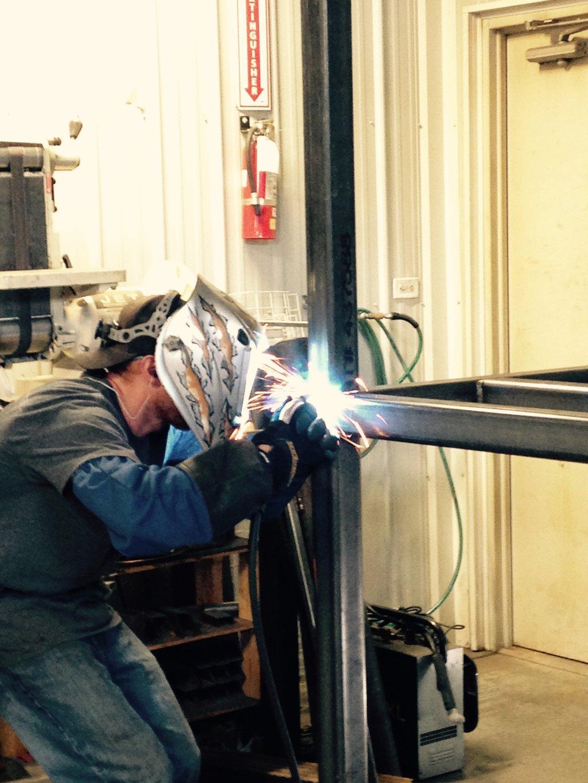Adam_welds_metal_coil_racks_for_Bridger_Steel